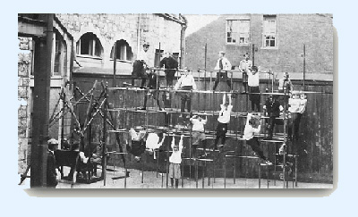 Large group of boys playing on a junglegym at rear of old school building.