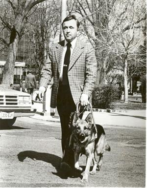 Robert Whitstock and dog guide crossing a city street. Photo courtesy of the Archives of the American Foundation for the Blind